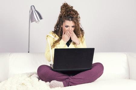 asombro: Mujer asombrosa de Trabajo latino con su computadora portátil sucia sentado en un sofá blanco.