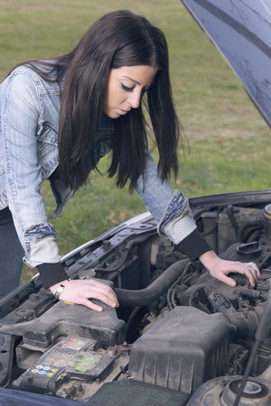 emergency vest: Woman standing next to a broken car trying to fix it worried
