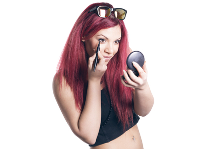 red haired woman: Red haired woman applyng eyeliner looking in a pocket mirror, smiling happy over white background. Stock Photo