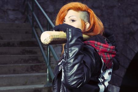 bat: Aggressive punk woman posing with a baseball bat against a dirty wall. Stock Photo