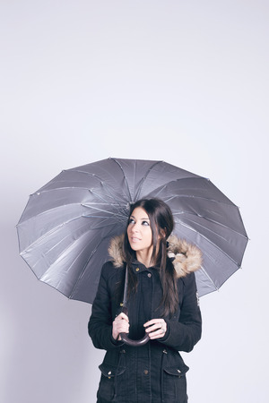 under: Happy woman wearing a coat, holding an umbrella, over gray background Stock Photo