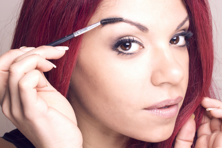 tinting: Portrait of a redhead beauty with a tool eyebrow tinting brush applicator
