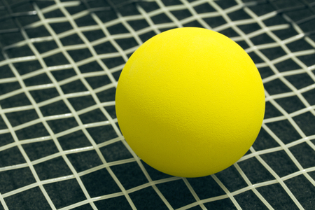 racquetball: Racquetball on racket strings. Yellow frontenis ball laying on racket strings, over black background.