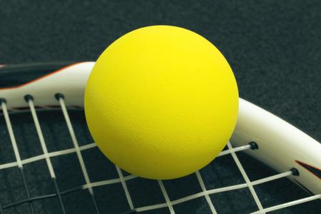 racquetball: Racquetball en cuerdas de la raqueta. frontenis bola amarilla que pone en cuerdas de la raqueta, sobre fondo negro.