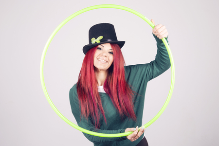 march 17th: Happy woman celebrating Saint Patricks day on march 17th, smiling with a green hula hoop. Stock Photo
