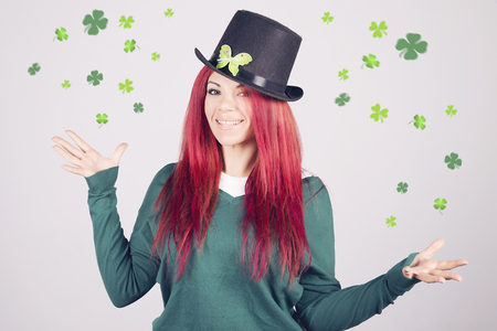 17th: Happy woman celebrating Saint Patricks day on march 17th, smiling surrounded by shamrocks and clovers. Stock Photo