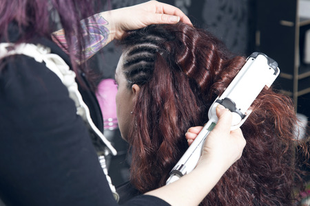 curler: Hairdresser ironing one customers curled hair with a electric hair curler. Stock Photo