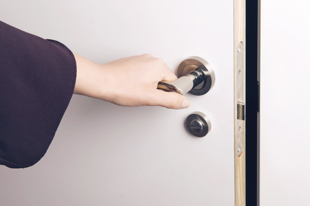 room door: Woman hand opens a door to a dark and unknown room. Concept: Making choices.