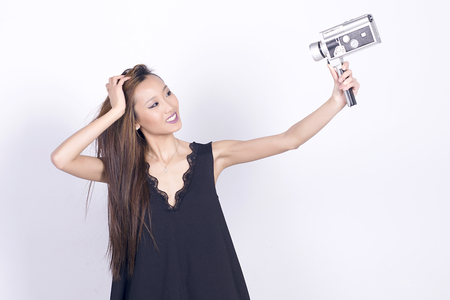 super 8: Lovely asian girl with vintage super 8 mm camera, taking selfie, making self portrait. Over white background.
