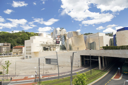 tramline: Bilbao, Spain - May 09, 2016: Exterior view of the south side of the Guggenheim Bilbao Museum. This Museum is dedicated exhibition of modern art. Editorial