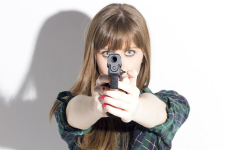 Blonde woman holding a pistol, aiming to camera, aggressive, over a white wall.