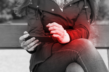 white color: Woman with a injured wrist wrapped in an bandage, using a smartphone feeling pain, outdoors. Black and white image, pain area of red color. Stock Photo