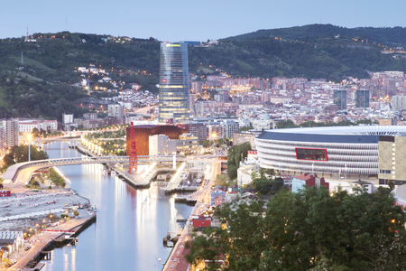 ria: Bilbao, Basque Country, Spain - May 24, 2016: View of the illuminated city of Bilbao in the sunset, with Nervion river, San Mames football stadium, Iberdrola tower, the Ria de Bilbao Maritime Museum, or the Euskalduna Conference Center.