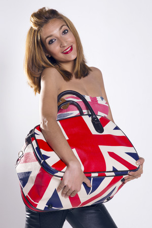 loves: Happy woman smiling and looking to camera, holding a bag with UK flag, and wears a shirt with the UK flag too. She loves UK!.
