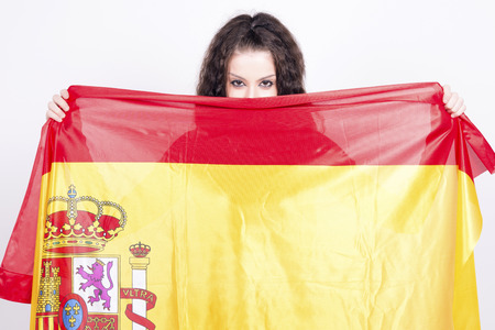 actual: Woman playing with a spanish flag, hiding behind. She is a Spain team supporter!. Actual flag, no add ons. Stock Photo