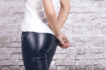 leather pants: Back view of a woman wearing leather trousers and a white shirt, over a white brick wall.