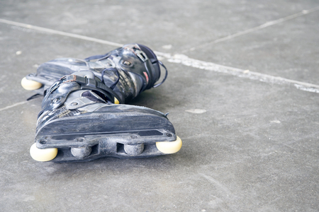 inline: Rollerblading. A pair of very used inline skates on the street.