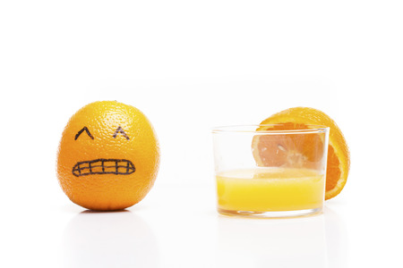 Stressed orange close to a glass of juice!. Funny moment.