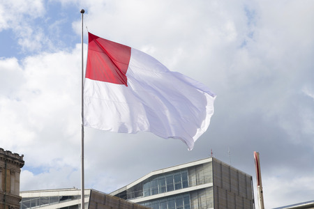 actual: Actual flag of the city of Bilbao, Spain. Fluttering in blue cloudy sky, located near the town hall.
