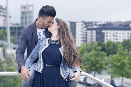 tenderly: Young couple in love outdoors, in the city near a group of trees. He is touching her hands, very close to her. They are kissing tenderly. Stock Photo