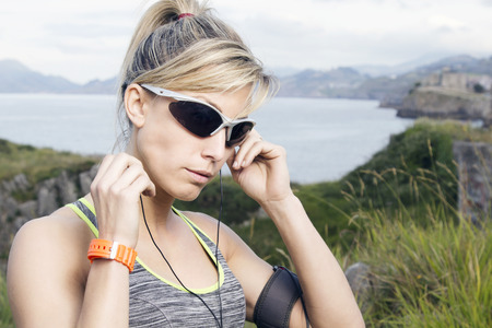 Female runner adjusting her earphones. Women fitness and jogging workout outdoors, in the mountain with the sea on the background.