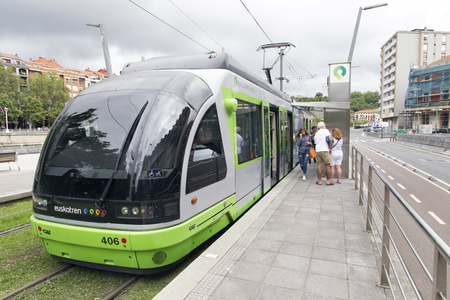 pio: Bilbao, Spain - July 05, 2016: One Bilbao tram station stopped on Pio Baroja. People entering and going out of the wagon.