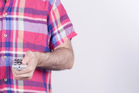 changing channel: Average man wearing a shirt, holding a remote control pushing buttons, changing channel or something in his life. Stock Photo