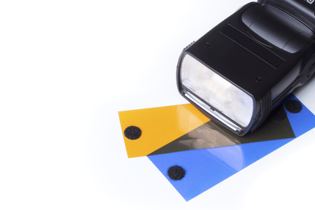 gels: Head of a camera flash, over a white background with two gels, orange (CTO) and blue (CTB). Stock Photo