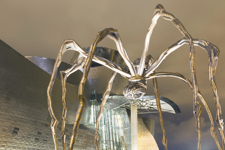 bourgeois: Bilbao, Spain - July 26, 2016: Exterior view at night of the north side of the Guggenheim Bilbao Museum. Detail of the head of the Mother sculpture by Louise Bourgeois.