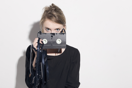 80s adult: Young blonde woman damaging a vhs tape, looking to camera behind the cassette, over a white background. Stock Photo