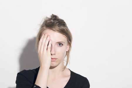 one eye: Young blonde woman covering half face with hand, looking to camera, over a white background.