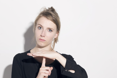 timeout: Young blonde woman with time-out sign, looking to camera, over a white background. Stock Photo