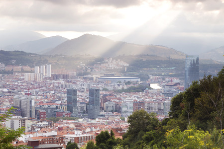 vizcaya: Bilbao, Spain - September 1, 2016: Sun rays touching the city of Bilbao. View of the downtown from a near hillside. We can see the Isozaki gate, San Mames football stadium or the Iberdrola tower. Stock Photo