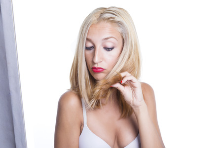 the ends: Woman and her blonde hair. Worried about her split ends. Over a white background. Isolated.