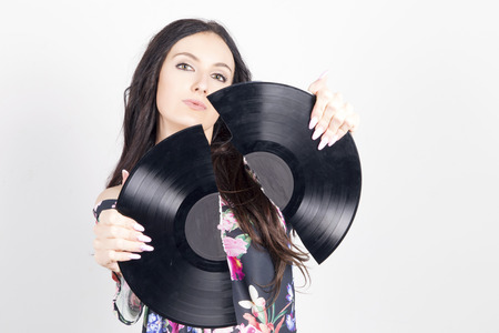 Young woman holding a broken vinyl record. Indoors, over a grey background. Selectrive focus, focus on her eyes.