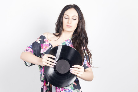 Young woman bending a vinyl record, trying to breaking it. Indoors, over a grey background. Stock Photo