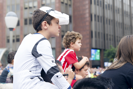 stormtrooper: BILBAO, SPAIN - SEPTEMBER 24, 2016 - Little boy dressed like a Stormtrooper, on His fathers shoulders, looking at a Star Wars Parade.