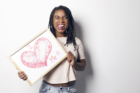 Happy young african woman holding an white board, with the I love me message written on it, over a white background. Banque d'images