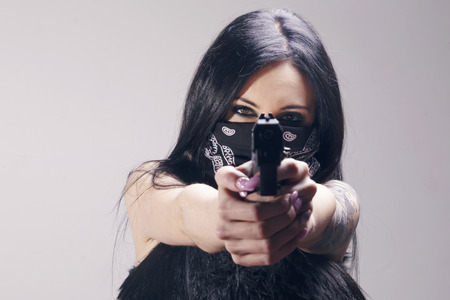 Beautiful brunette woman with a pistol pointing to camera, wearing a bandana as a thief, looking at menacing. Over a gray background.