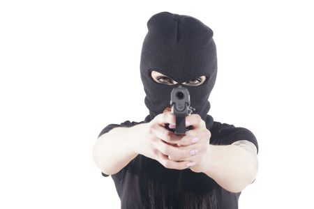 Aggressive woman with a black balaclava, pointing to camera with a pistol. Isolated, over a white background. Shallow depth of field, focus on her eyes.