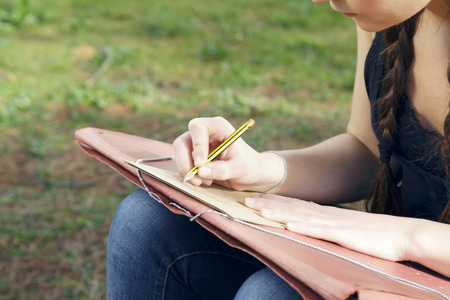 Young brunette woman artist, drawing sketch and thinking, looking for inspiration. Outdoors, in nature. Stock Photo