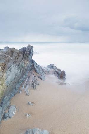 basque country: Serene seascape in Arrietara beach, Biscay, Basque Country, Spain. Long exposure on a cloudy sunset.