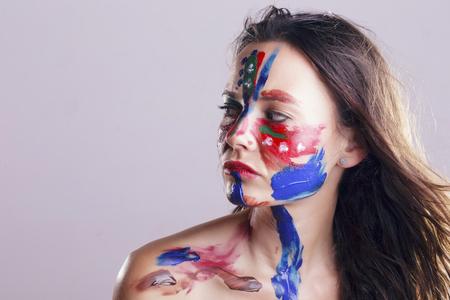 Fille avec son visage peint, huile acrylique colorée avec ses propres mains, en faisant des motifs aléatoires. En studio, sur un fond gris. Banque d'images - 80887701