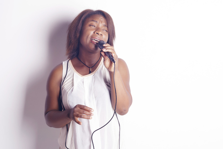 Young african woman singing holding a microphone, cheerful and funny, indoors, over a white background.