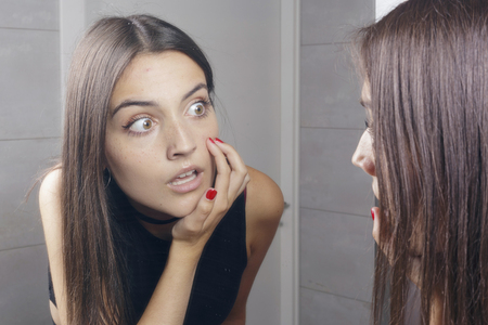 Surprised young woman finding acne on her face, standing before a mirror looking at her reflection. Indoors. Stock Photo