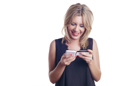 Woman with a credit card using a white smart phone. Online shopping, indoors. Over a white background, isolated.
