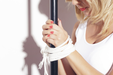 Blonde woman standing with her hands bound to a black metallic tube with a white rope. Indoors over a white background. Stock Photo