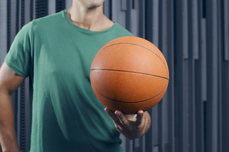 Confident man standing over a metallic background, with a basket ball, outdoors.