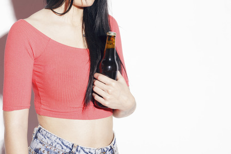 Young woman with dark hair in blue jeans, holding a unopened bottle of beer, over a white background, in studio. Banque d'images