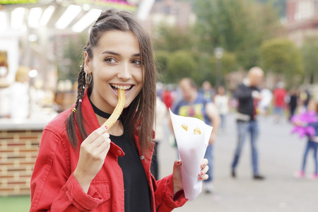 Cheerful brunette girl in the town fair, eating traditional spanish snack named